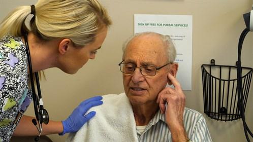 Tanis Bergen, LPN asks patient Fred Johannson about his hearing.