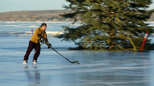 A man skates on a frozen Sylvan Lake.  Sylvan Lake is a popular tourist destination in summer.