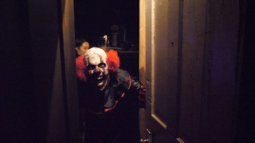 A scary clown greets post secondary students from Calgary at Creepy Hollow, north or Warner, AB, just before Halloween.