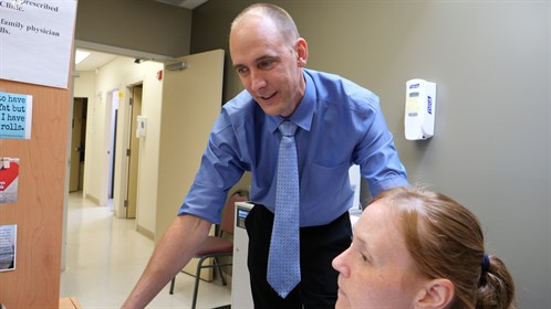 Dr. Hendrik van der Watt meets with a medical office assistant at his clinic in Bonnyville.