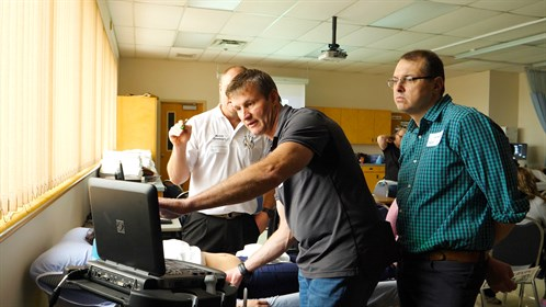 Dr. Stefan Badenhorst (C) points to screen while instructor Dr. Andries Esterhuizen (L) and Dr. Dr. Thian Müller (R) look on.